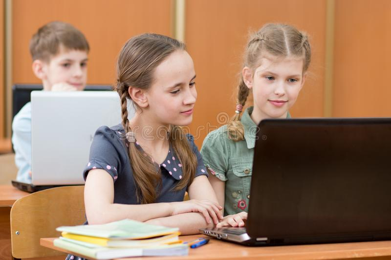 Happy kids at laptop in the classroom royalty free stock photography