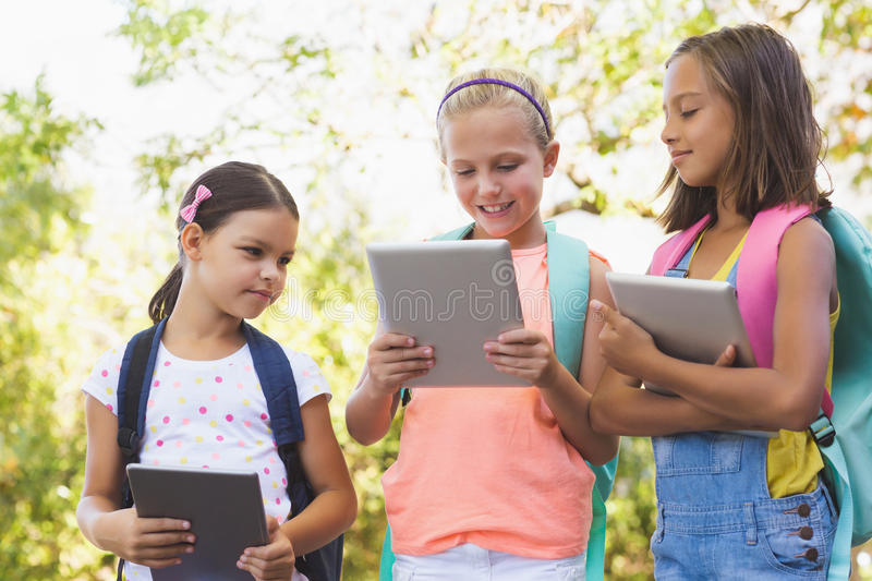Happy school kids using digital tablet stock photography