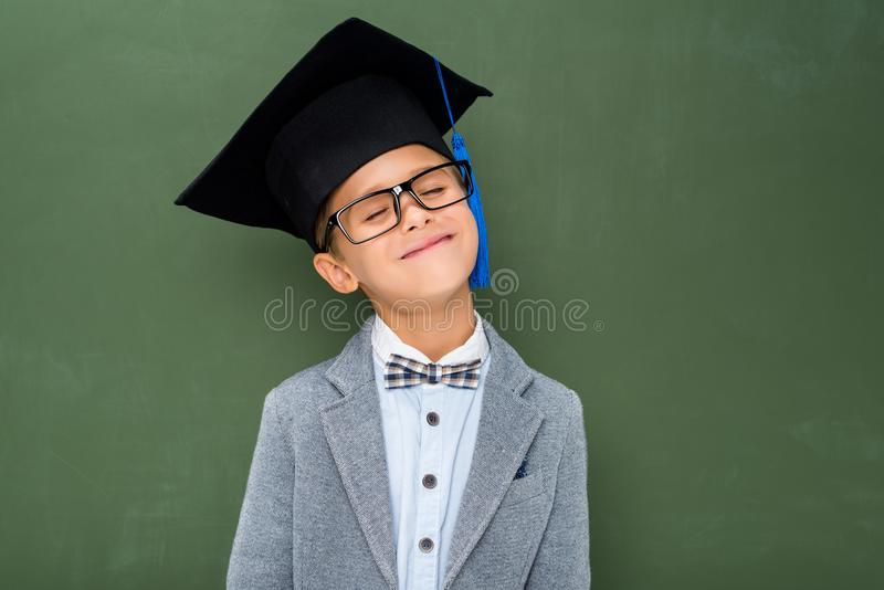 Happy schoolboy in graduation hat stock photography