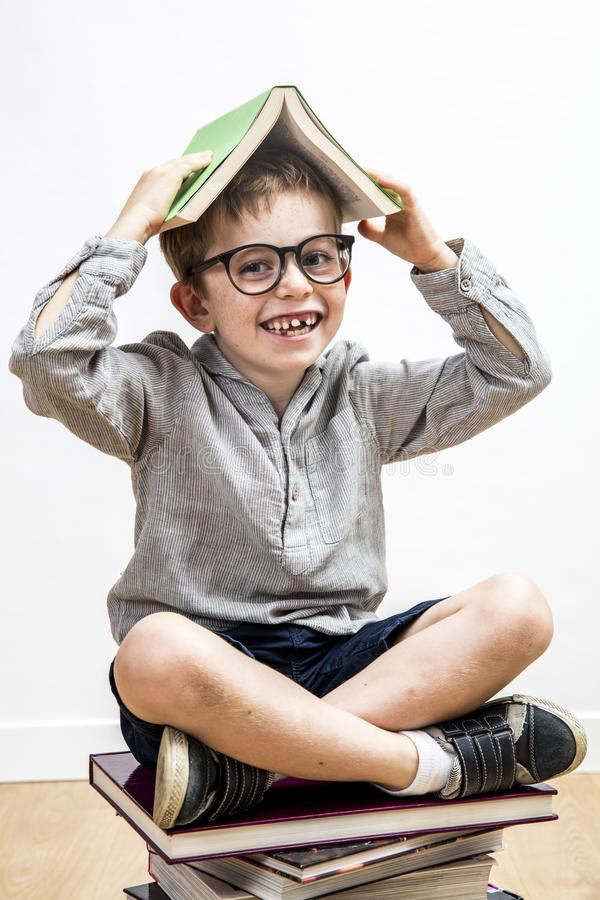 Happy schoolboy with missing tooth covering his head with book. Happy 6-year old schoolboy with a missing tooth and eyeglasses covering his head with a book stock photo