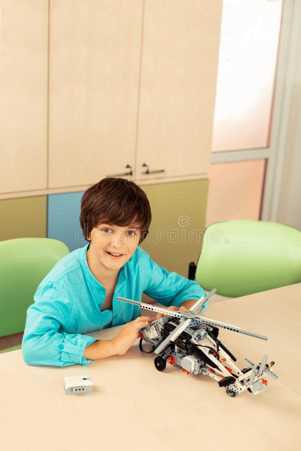 Happy schoolboy showing his new helicopter model. royalty free stock photography
