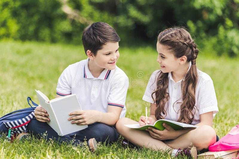 happy schoolchildren doing homework together while sitting on grass stock images
