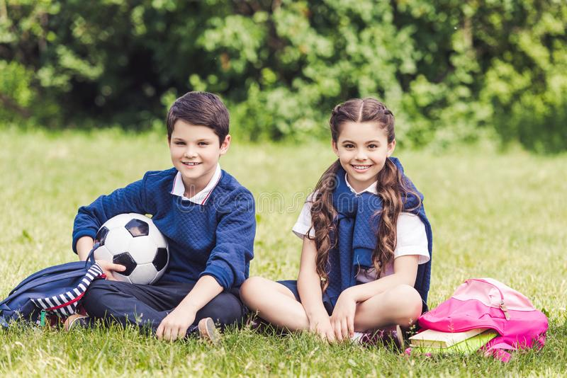 Happy schoolchildren sitting on grass in park with backpacks. And soccer ball stock images