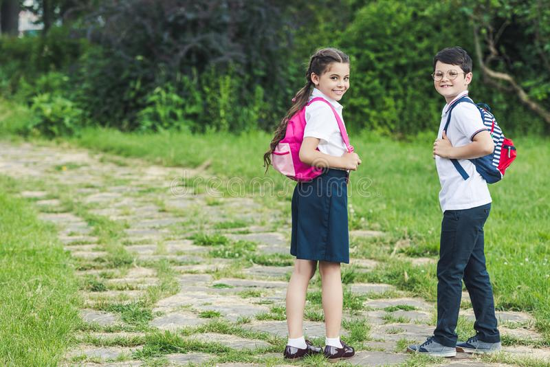 Happy schoolchildren spending time together. In park stock photography