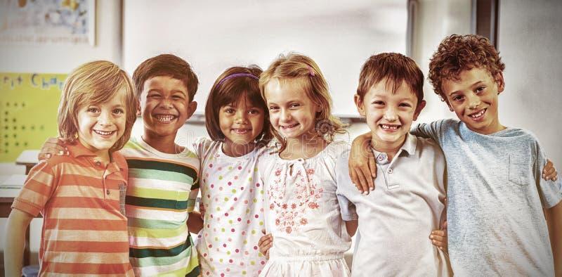 Happy schoolchildren standing in classroom stock images