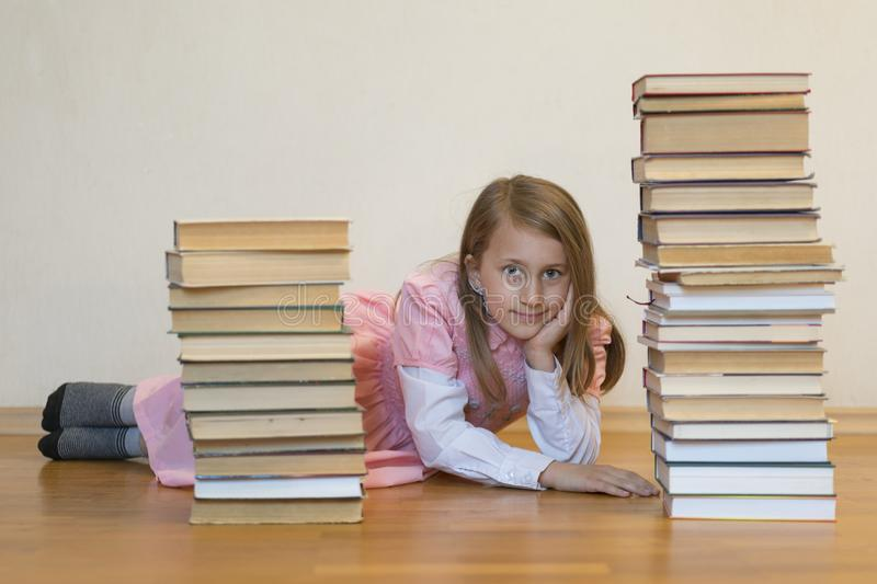 Happy schoolgirl with books in the room. Education concept. back to school. Girl in a pink dress with books royalty free stock photo