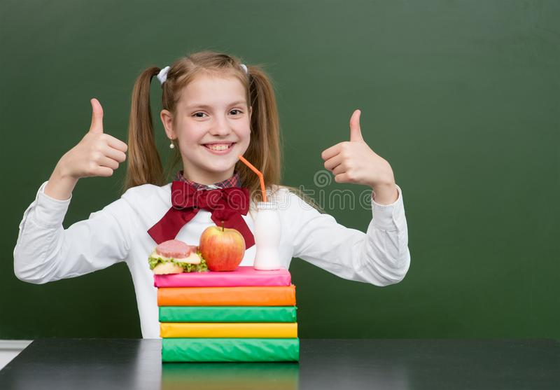 Happy schoolgirl with food in classroom showing thumbs up.  royalty free stock image