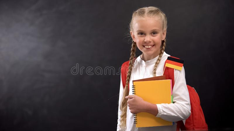 Happy schoolgirl holding books with German flag, ready to learn foreign language. Stock photo stock photos