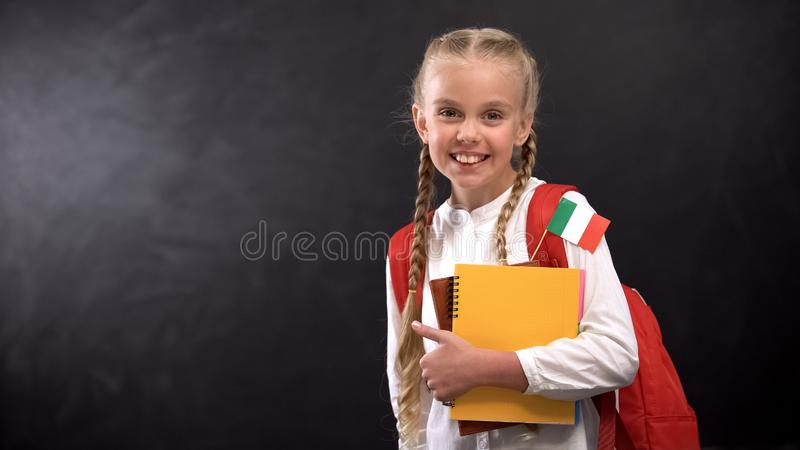 Happy schoolgirl holding books with Italy flag, ready to learn foreign language. Stock photo royalty free stock photography