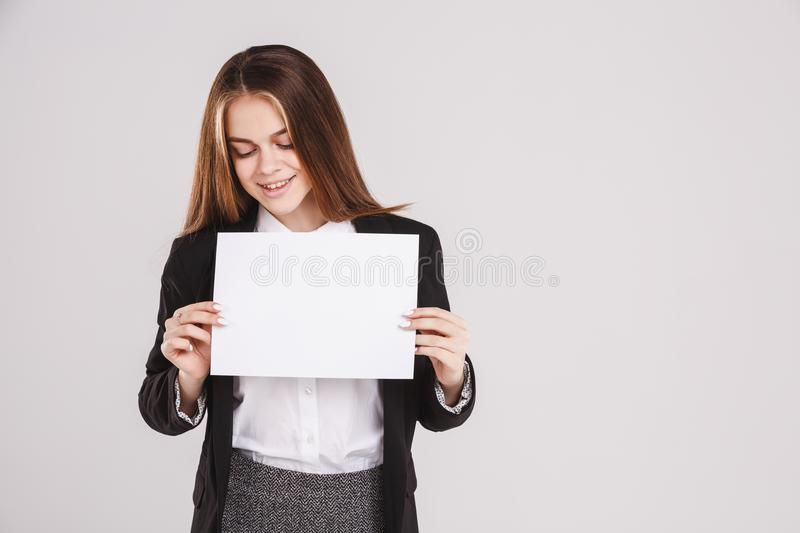 Happy schoolgirl holding an empty paper sheet suitable for text. Isolated on white background. Copy space stock photo