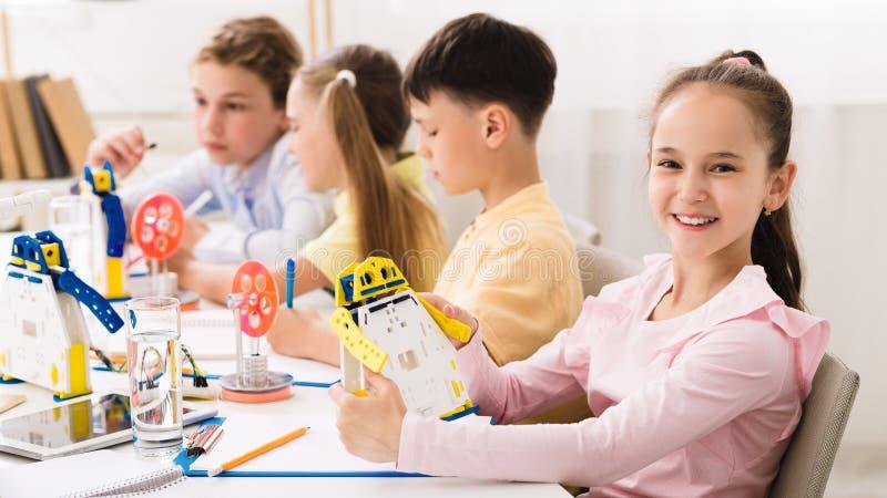Happy schoolgirl holding robot model in classroom royalty free stock photography