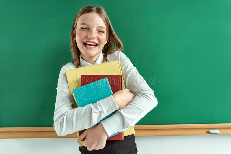Happy schoolgirl likes read a books. Photo of student with books, creative concept with Back to school theme stock photography