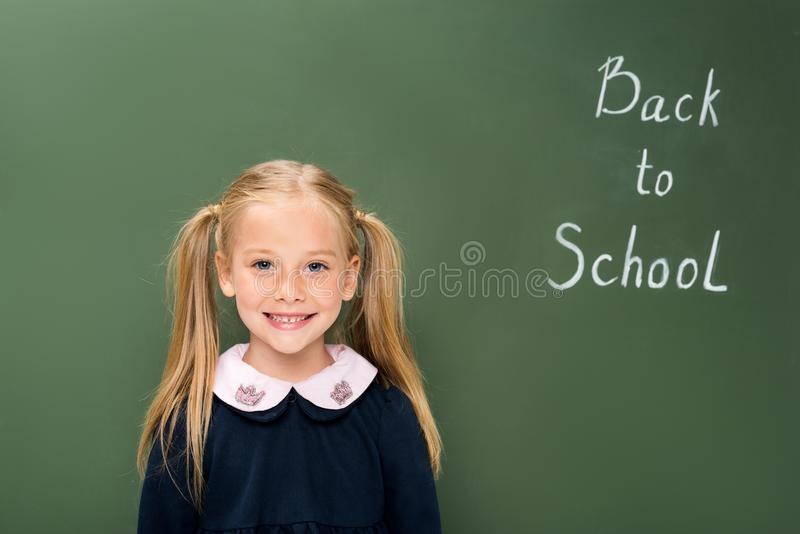 Happy schoolgirl next to chalkboard. With back to school sign royalty free stock photo