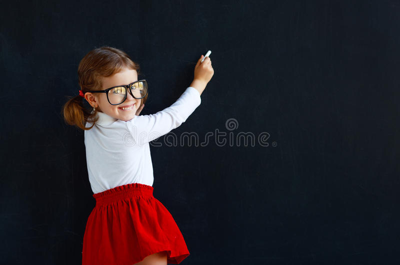 Happy schoolgirl preschool girl near school blackboard. Happy schoolgirl preschool girl near school board blackboard royalty free stock image