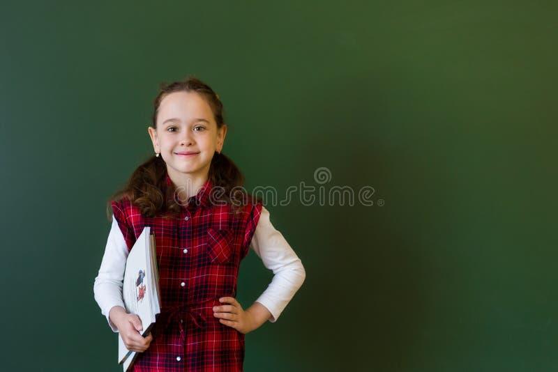 Happy schoolgirl preschool girl in plaid dress standing in class near a green blackboard. Concept of school education royalty free stock photo