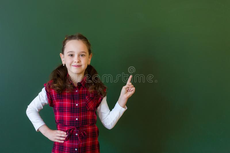 Happy schoolgirl preschool girl in plaid dress standing in class near a green blackboard. Concept of school education royalty free stock photo