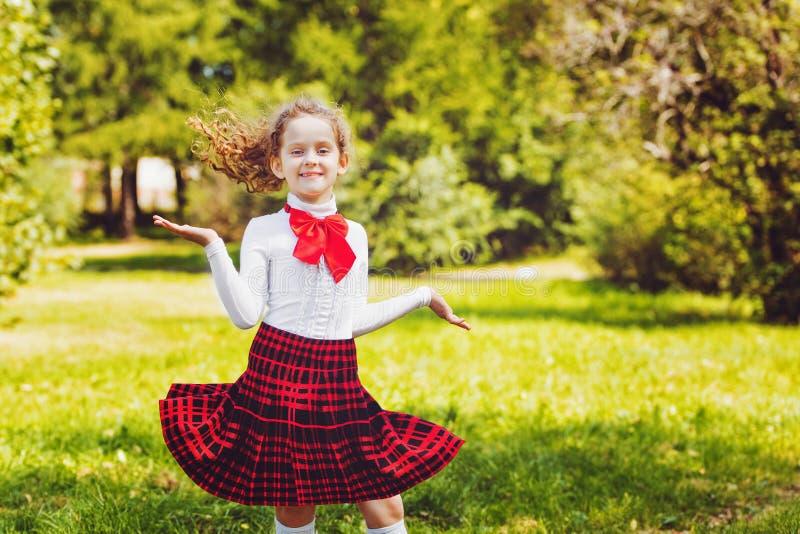Happy schoolgirl in school uniform jump in the park. stock photos