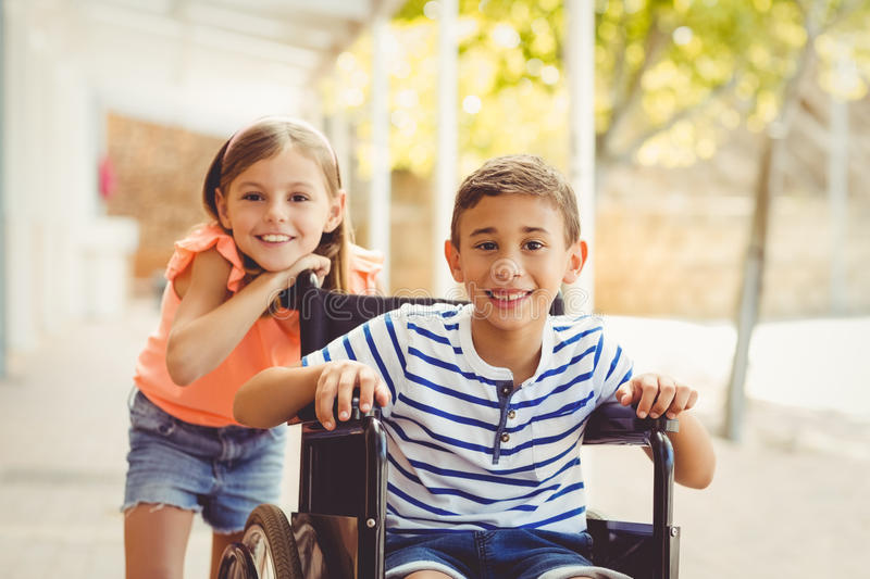 Happy schoolgirl standing with schoolboy on wheelchair royalty free stock image