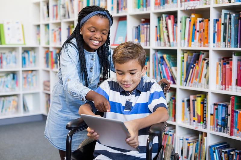 Happy schoolgirl standing with schoolboy on wheelchair using digital tablet. In library royalty free stock photos