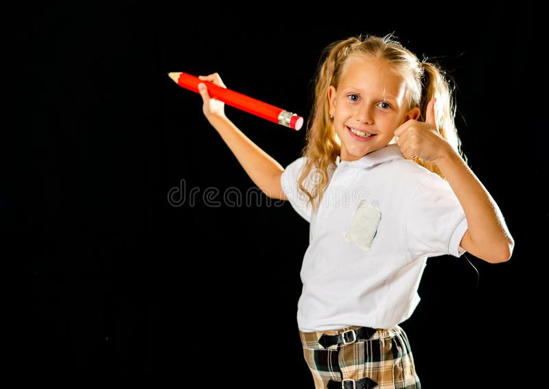 Happy schoolgirl writing on the blackboard with thumb up gesture stock photography