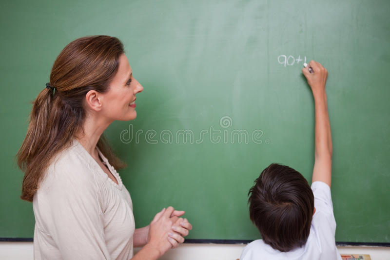 Happy schoolteacher helping a schoolboy doing an addition royalty free stock photos