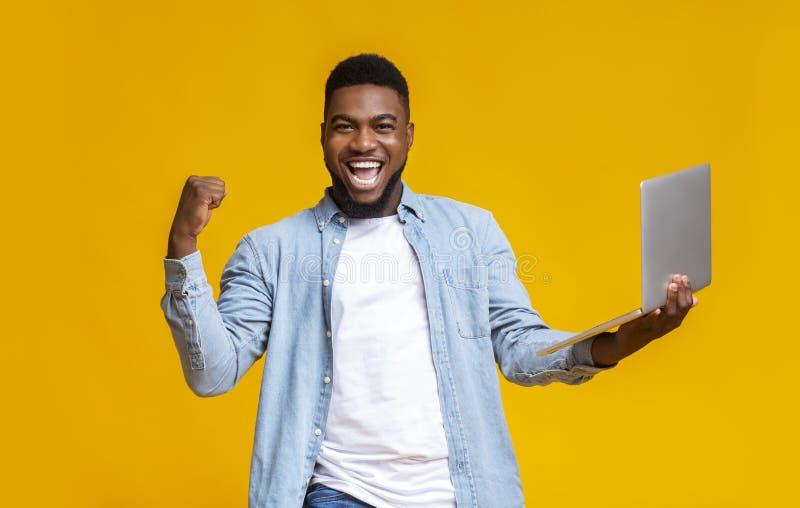 Happy schwarzer Kerl freut sich über Erfolg mit Laptop stockbild