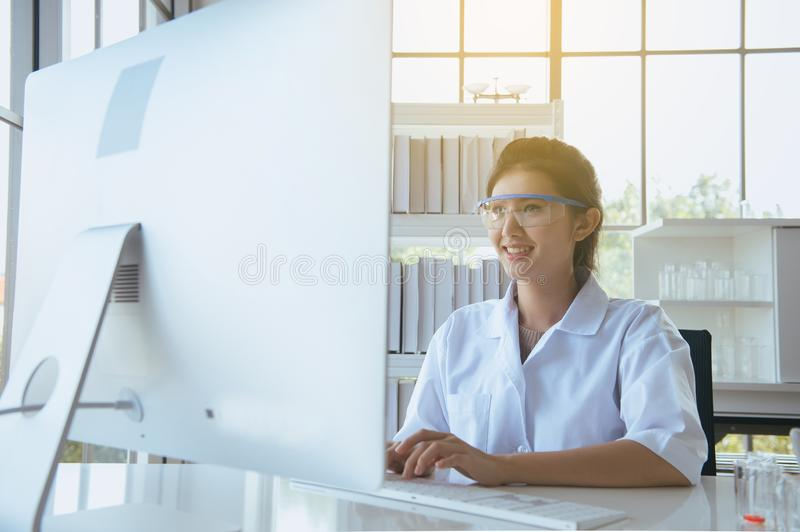 Happy scientist asian woman working and using computer keyboard on desk in office room,Finger typing close up stock images