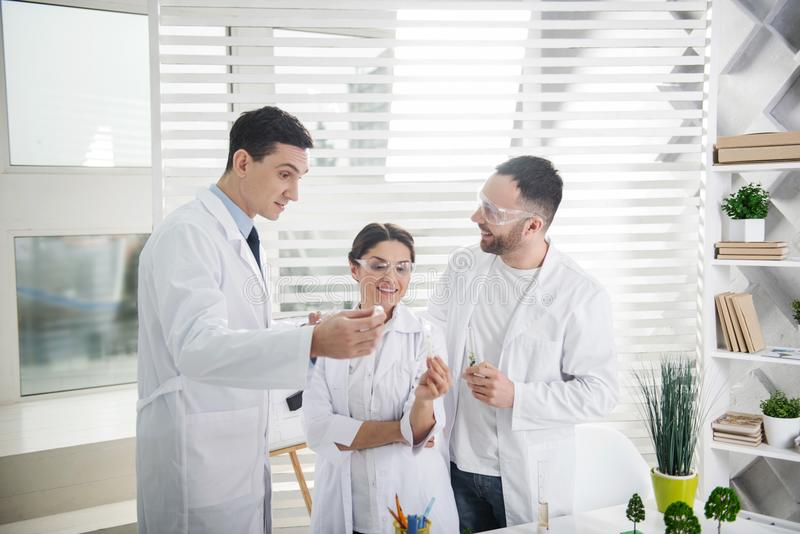 Happy scientist delighted with test results. Happy with results. Delighted professional experienced scientists smiling and wearing uniforms and holding test royalty free stock image