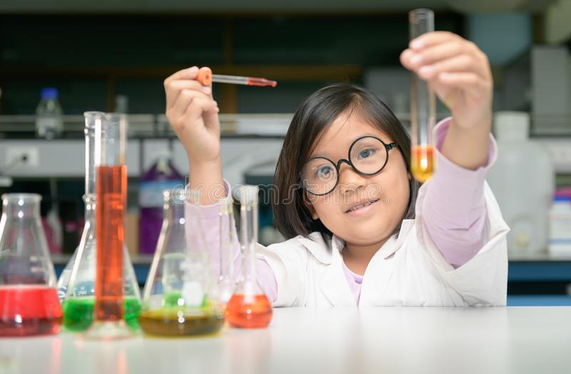 Happy scientist girl making experiment with test tube stock images