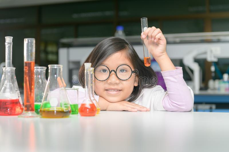Happy scientist girl making experiment with test tube stock photography