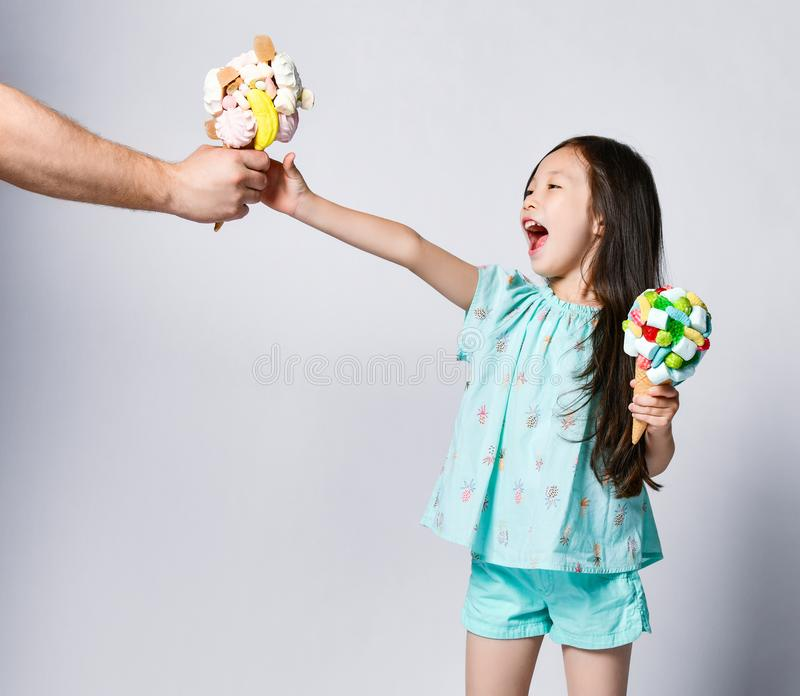 Happy screaming baby girl kid is glad to take another one big ice-cream in waffles cones with tasty toppings that man gives her. Happy screaming baby girl kid is stock photo
