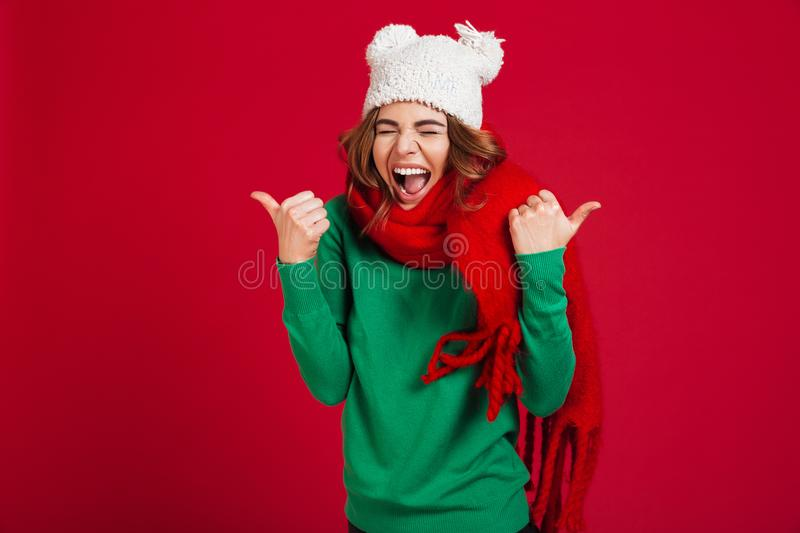 Happy screaming brunette woman in sweater, funny hat and scarf stock photography