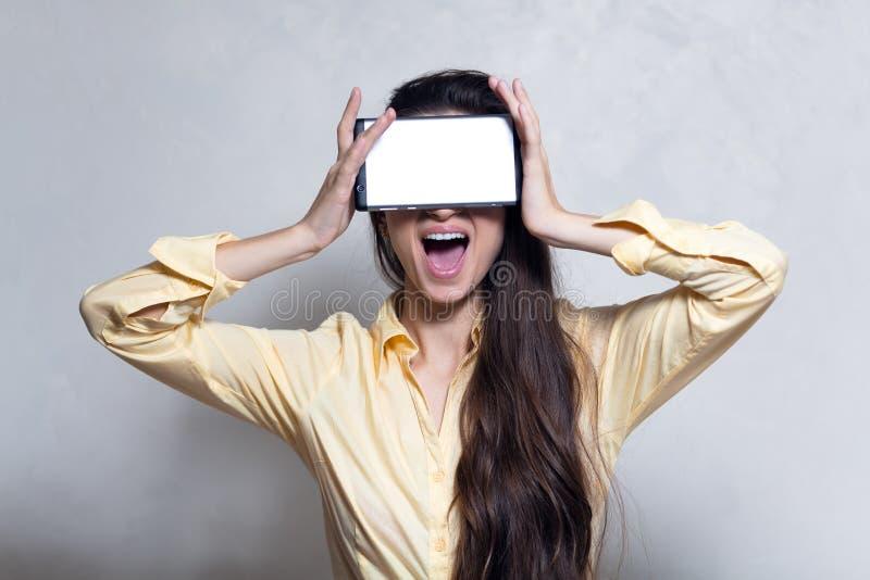 Happy screaming girl holdin smartphone on eyes. stock photo