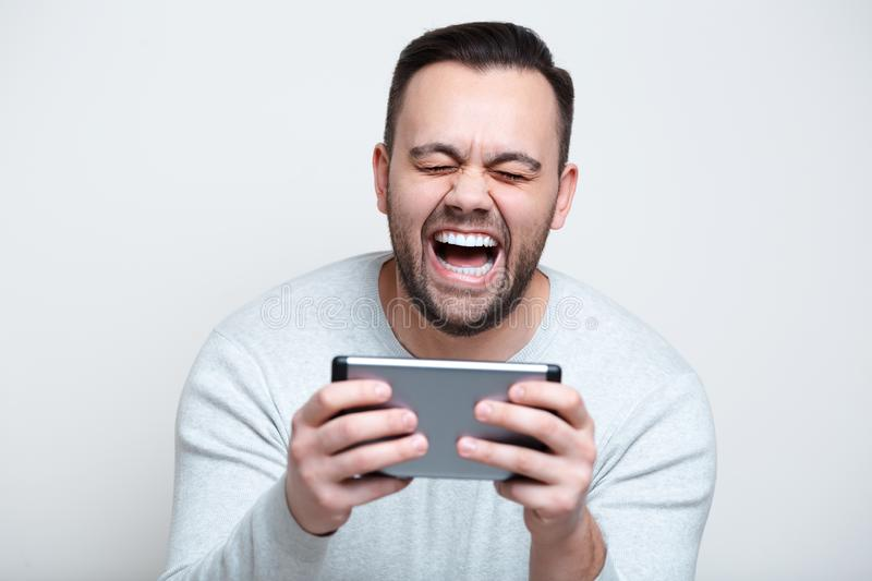 Happy screaming man playing video games on smartphone over white background stock image