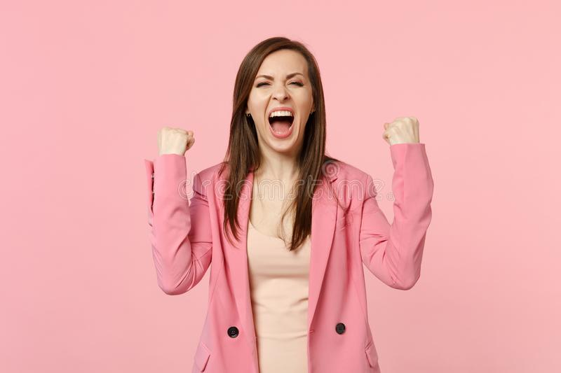 Happy screaming young woman in jacket clenching fists like winner expressive gesticulating with hands isolated on pastel. Pink background. People sincere stock photos