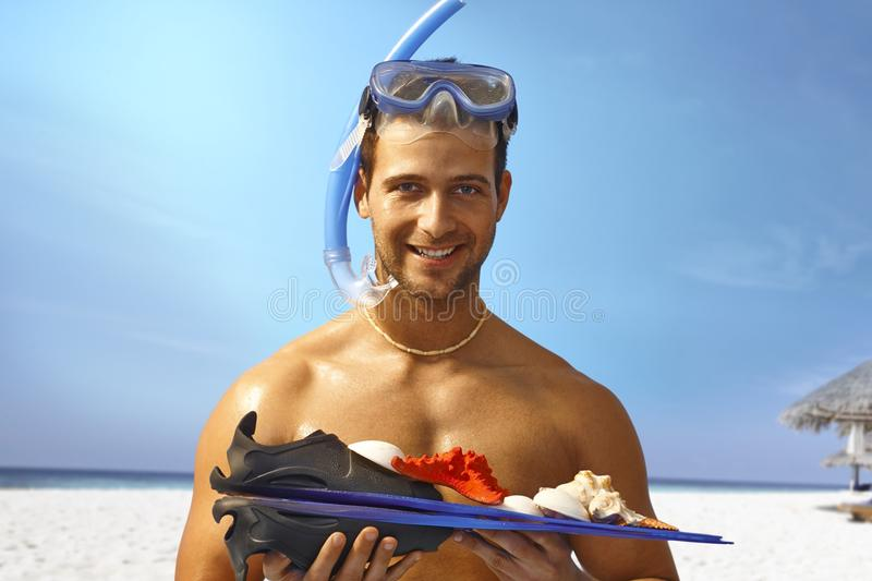Happy scuba diver holding seashells royalty free stock photo