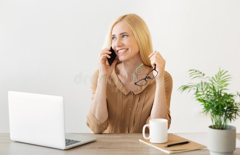 Happy Secretary Calling On Smartphone In Office royalty free stock photo