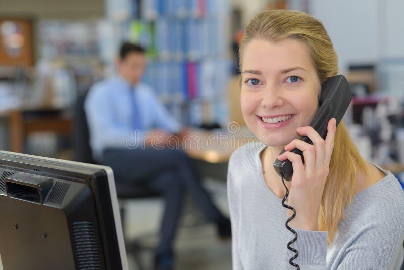 Happy secretary in office phoning stock photography
