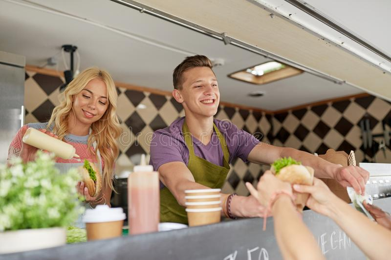 Happy sellers serving customers at food truck. Street sale and people concept - happy young sellers serving customers at food truck stock photo