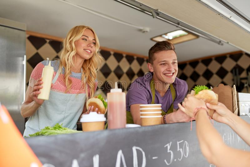 Happy sellers serving customers at food truck. Street sale and people concept - happy young sellers serving customers at food truck stock photography