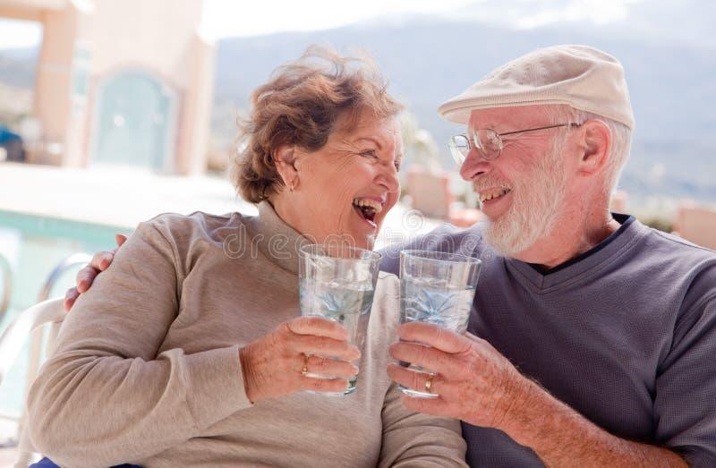 Happy Senior Adult Couple with Drinks. Happy Senior Adult Couple Enjoying Drinks Together stock photos