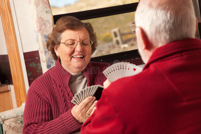 Happy Senior Adult Couple Playing Cards in Their Trailer RV. Happy Senior Adult Couple Playing Cards in Their Travel Trailer RV stock images