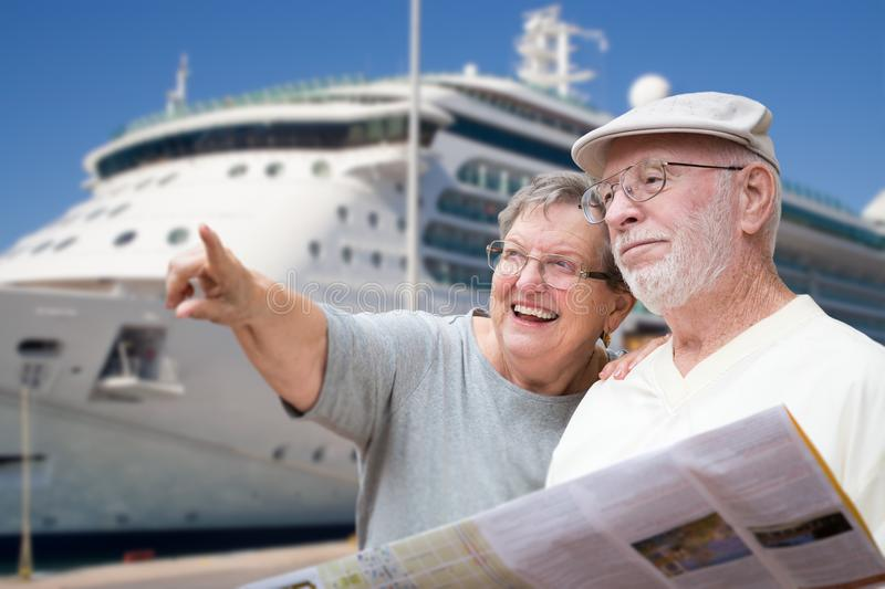 Happy Senior Adult Couple Tourists with Brochure by Cruise Ship. Happy Senior Adult Couple Tourists with Brochure Next To Passenger Cruise Ship royalty free stock image