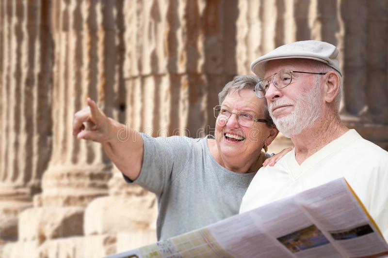 Happy Senior Adult Couple Tourists with Brochure Next To Ancient. Column Ruins royalty free stock images