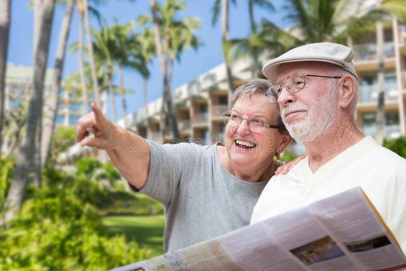 Happy Senior Adult Couple Tourists with Brochure. Next To Tropical Hotel and Palm Trees royalty free stock photo