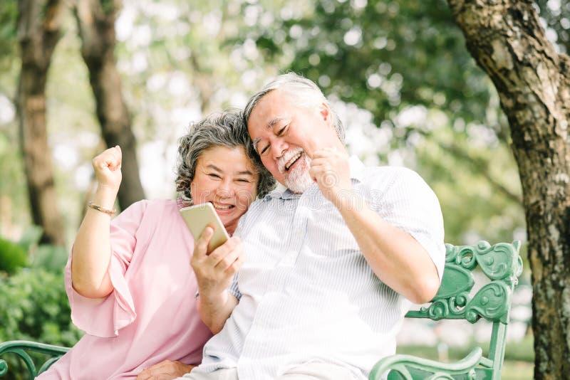 Happy senior Asian couple using smartphone stock image