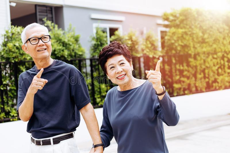 Happy senior Asian couple walking and pointing in outdoor park and house. Warm tone with sunlight. royalty free stock photography