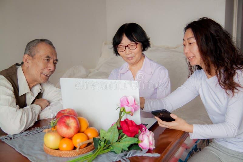 Daughter and senior parents using laptop at home. stock photos
