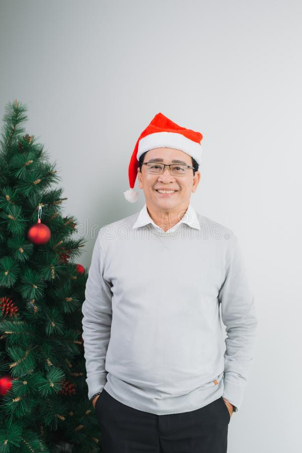 Happy senior asian man standing by christmas tree at home. stock photography