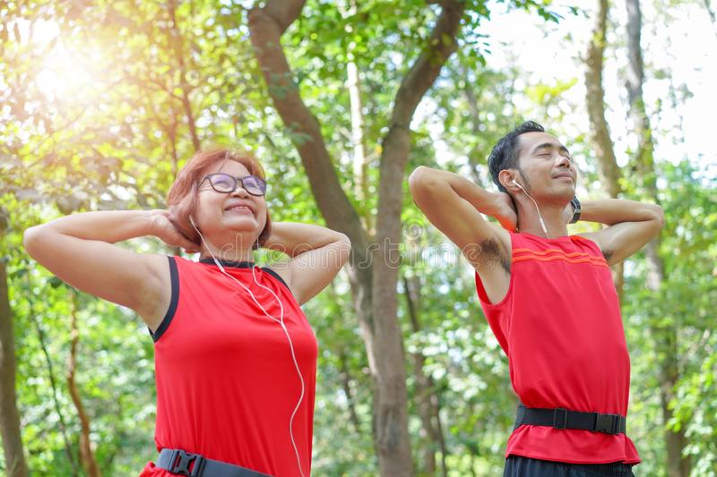 Happy senior asian woman with man or personal relaxed listening to music in the park royalty free stock photos